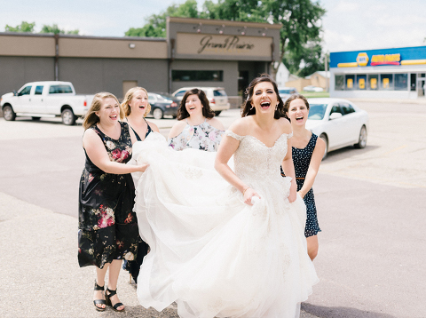 Candid wedding photography Bride laughing with personal attendants carrying her train through downtown Luverne, MN