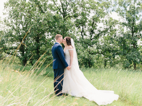 Bride and Groom kissing in tall grass Minnesota Blue Mounds State Park wedding photography