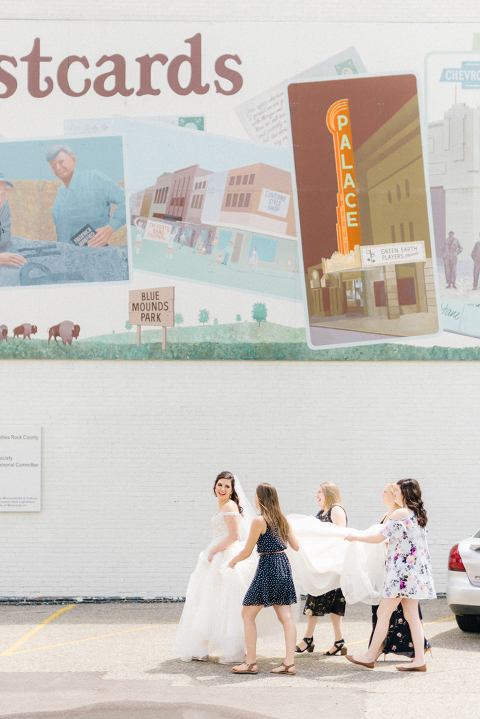 Natural relaxed wedding photography Bride with personal attendants laughing in front of mural