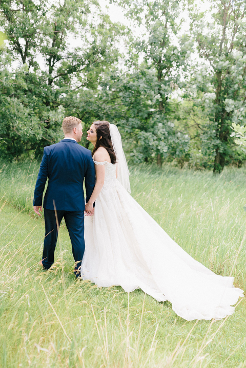 Bright and airy Luverne, MN wedding photography bride and groom walking through prairie grass