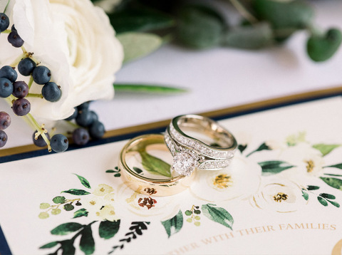 Gold and silver wedding rings set on garden theme invitations vineyard ceremony Iowa photography