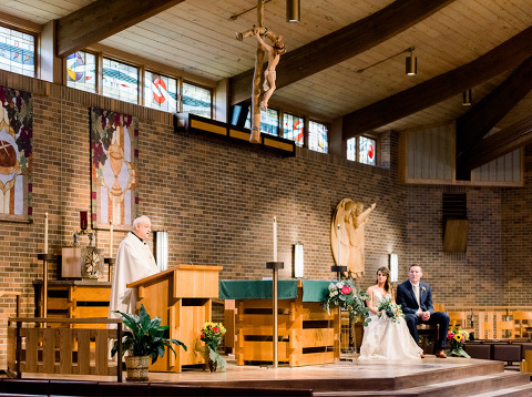 Bride and groom sitting on altar Sioux Falls wedding photography St. Michael's Catholic Church