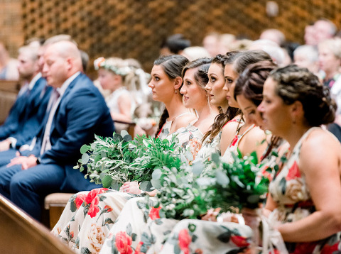 Bridesmaids floral print boho dresses and greenery bouquets lined up in pew St. Michael's Catholic Church Sioux Falls