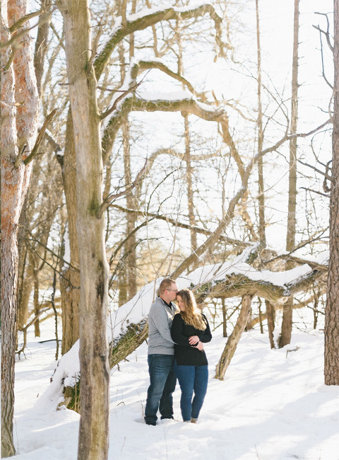 Engagement pictures in nature snowy trees kiss on forehead